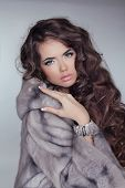 stock photo of mink  - Beautiful brunette girl wearing in mink fur coat with long hair styling isolated on grey background - JPG
