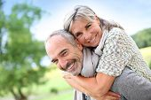 stock photo of piggyback ride  - Senior man giving piggyback ride to woman - JPG