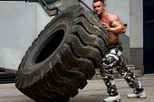 foto of strongman  - Muscular Man with Truck Tire doing crossfit style workout turning tire over - JPG