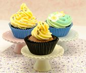 stock photo of torta  - Cupcakes decorated with butercream of some colors in blur background - JPG