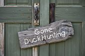 stock photo of fowl  - Old gone duck hunting sign on doorway - JPG