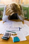 stock photo of revenue  - a woman with unpaid bills has many debts - JPG
