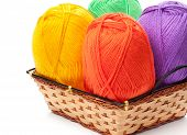 four yarn skeins in yellow, orange, green, purple colors in basket on white background