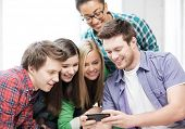 education and technology concept - group of students looking at smartphone at school