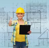 repair, construction and maintenance concept - smiling woman in helmet with clipboard showing thumbs