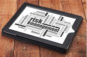 risk management word cloud - a digital tablet on a rustic wooden table
