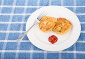 image of cooked blue crab  - Two browned crab cakes on a white plate with fork and cocktail sauce on a blue towel - JPG
