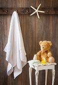 Childrens bathroom with hanging white towel and teddy bear