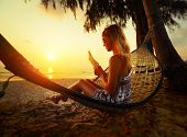 Young woman reading the book in the hammock on tropical beach at sunset