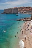 DUBROVNIK, CROATIA - MAY 28, 2014: People on Banje beach with Old town in background. Banje is most popular beach in Dubrovnik very close to town.