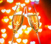 A Pair Of Champagne Flutes With Golden Bubbles On Hearts Bokeh Background