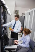Team of technicians using digital cable analyser on servers in large data center