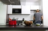 Back view of man standing in kitchen