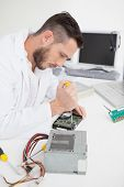 Computer engineer working on broken cpu with screwdriver in his office