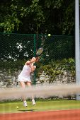Pretty tennis player serving the ball on a sunny day
