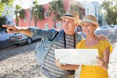 Happy tourist couple using map in the city on a sunny day