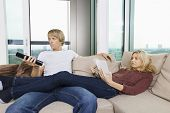 Relaxed couple reading book and watching TV in living room at home