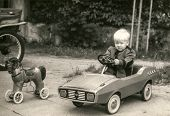 POLAND, CIRCA eighties: Vintage photo of little boy in toy car