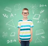 vision, education, childhood and school concept - smiling little boy in eyeglasses over green board