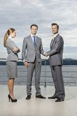 Full length portrait of young businessmen shaking hands while businesswoman looking at them on terra