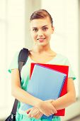 happy student girl with school bag and notebooks