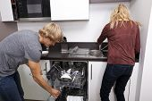 Caucasian couple working together in kitchen