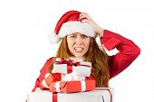 Festive stressed redhead holding gifts on white background