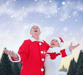 Festive mature couple against snowy landscape with fir trees