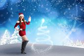 Sexy santa girl pointing against snowy landscape with fir trees