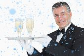 Waiter holding tray with glasses full of champagne against snow falling