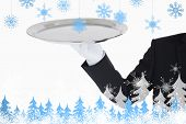 Hand with white gloves holding a silver tray against snowflakes and fir trees