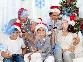 Family celebrating Christmas with wine and sweets at home against snowflakes