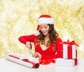 christmas, holidays, celebration, decoration and people concept - smiling woman in santa helper hat with scissors packing gift box over yellow lights background