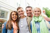 travel, vacation and friendship concept - group of smiling friends in city
