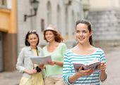 tourism, travel, leisure and holidays concept - smiling teenage girls with city guide, map and camer