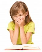 Cheerful young girl is reading book and covering her mouth laughing, isolated over white