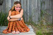 Young beautiful hippie girl sitting near a house outside the city (with space for text)