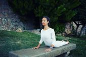 Healthy woman in white clothes meditating and exercising
