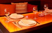 Glass dining table with orange backlight in a restaurant