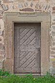 Old wooden door with stone portal