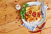 picture of enchiladas  - Enchiladas with cream and red peppers on wooden table ready to serve - JPG