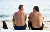 two men sitting on beach and chatting