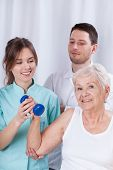Physiotherapist Insuring Senior During Exercise