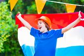 pic of holland flag  - Happy Dutch boy football fan cheering and supporting soccer team of Netherlands during championship celebrating sports victory screaming Hup Holland with national flag - JPG