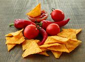 Tasty nachos, red tomatoes and chili pepper on wooden background