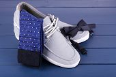 Top-Siders, socks and bow-tie on dark blue wooden background