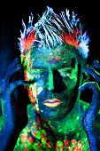 Body art glowing in ultraviolet light, unfocused