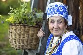 Old woman in Slav folk costume near a village house, a basket of flowers in the background.