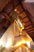 stock photo of recliner  - Half view of reclining buddha in Wat Pho of Bangkok Thailand - JPG