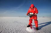 image of auger  - Ice fisherman drilling a hole with a power auger on a frozen lake - JPG